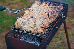 Many turkey roast meat pieces with onion on grill stock photography