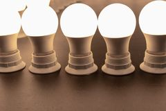 Many turned on, lighted bulbs with lampholders close up. stock images