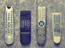 Many TV remotes on a gray concrete table. Top view. Remote control of home appliances and electronics stock photo