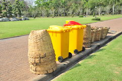 Many types of bin such as bamboo baskets, yellow wheeled bins stand on the edge of walk way for keep a trash Royalty Free Stock Photos