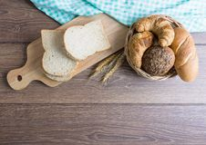 Many types of bread. Including croissants, whole wheat rolls, whole wheat bread, on a wooden cutting board and wicker baskets. All placed on wooden floors and royalty free stock photo