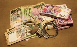 Many Ukrainian money hryvnia. Handcuffs on the money. Corruption in Ukraine. The fight against corruption. Physical evidence of. Corruption in government and royalty free stock photography