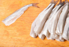 Many uncooked trunk small fish on wood Royalty Free Stock Photography