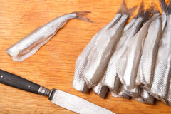 Many uncooked trunk small fish on wood Stock Photos