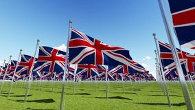 Many United Kingdom flags waving in the wind in green field. View from above. Three dimensional rendering animation stock video footage