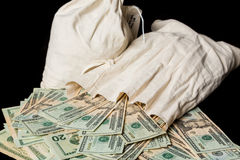 Many US dollar bills or notes with money bags Stock Photo