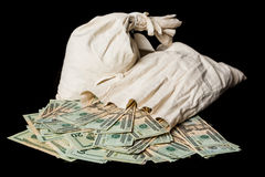 Many US dollar bills or notes with money bags Stock Photos