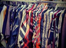 Many used clothes hanging in the flea market stall. And many other used clothes royalty free stock images