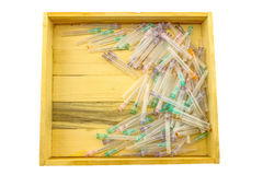 Many used disposable needle lie strewn in brown wooden box  isol Royalty Free Stock Image