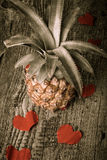 Many Valentine hearts with ananas on the old wooden table. Toned Royalty Free Stock Image