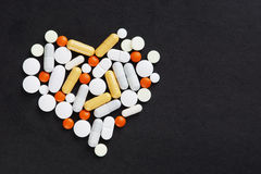 Many various pills and tablets as a heart on black background Stock Image