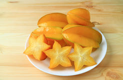 Many vibrant color ripe whole fruits and sliced Star Fruit on a white plate. Served on wooden table Royalty Free Stock Photo