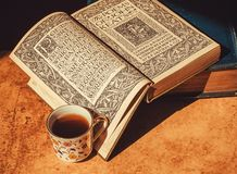 Many vintage books and 18th century volume the Poems of John Keats and floral design cup of coffee. Selective focus Stock Photo