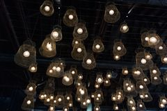 Many vintage incandescent glowing light bulbs with net lampshade hanging from the ceiling on the dark background texture. In restaurant interior royalty free stock photos