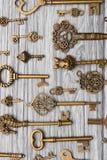 Many vintage keys on a light wooden background, vertical frame.  royalty free stock photography
