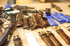 Many vintage watch straps on wood table for repair. Stock Photos