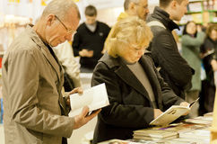 Many visitors holding books in bookstore Stock Photo