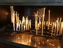 Many votive candles lit by the faithful in church. As religious supplication stock photos