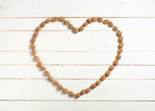Many Walnuts in Heart Shape in flat lay on distressed White Board Background with empty room or space for copy, text, your words Royalty Free Stock Photos