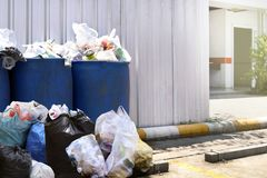 Many waste pile at plastic bin blue color for recycle garbage waste outdoors front zinc wall, plastic bin of garbage, bin trash. The many waste pile at plastic stock images