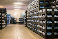 Many water bottles. Rows of crates at storehouse. Good quality guarantees profit. Merchandise supplied to shops Stock Image