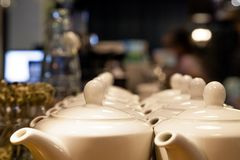 Many white ceramic teapots with round lids stand on the wooden b royalty free stock photos