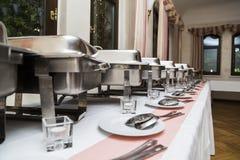Many white metallic clean modern utensils on wedding buffet stock photography