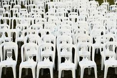 Rows of White Plastic Outdoor Chairs. Many white plastic outdoor furniture chars in rows after an outdoor concert or performance, some with post concert litter stock photography