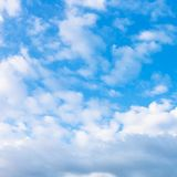 Many white puffy clouds in blue evening sky Royalty Free Stock Photos