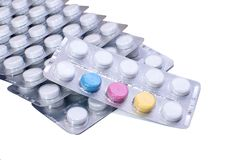 Many white and some colored pills in blister packs. Closeup stock photography