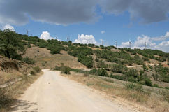 Many white wind turbines on the mountain with treed slopes and the earth road on foreground. Royalty Free Stock Photo