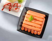 Many wiener sausages on a plate. Many wiener sausages on a plate and gray table Royalty Free Stock Photo