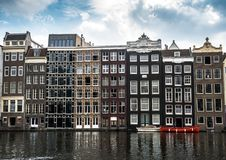 The many windows of Amsterdam canal houses on the water in summer. royalty free stock photos