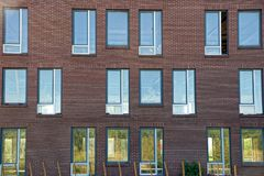 Many windows on a brown brick building wall. Facade of a large residential brick building with many windows Royalty Free Stock Photos