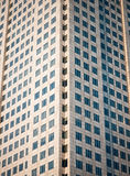 Many windows from the high-rise building. Shot in symmetric composition from a public road Stock Images