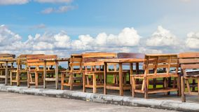 Many wood benches with sky clouds. Many wooden benches and benches are laid out in rows on the concrete e of the road, which has a sky background stock photos