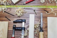 Many wooden bricks full of sawdust. On old scratched wooden table, work tools concept.  royalty free stock photo
