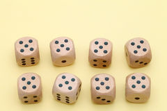 Many wooden dice. On a yellow backgroun Stock Photo