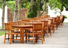 Many wooden tables and chairs. On terrace in hotel restaurant Stock Photos