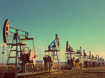 Many working oil pumps in row - vintage retro style Royalty Free Stock Images