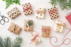 Many wrapped Christmas gift boxes bakers twine & spruce on white table. Many Christmas gift boxes, bakers twine & spruce on white table. Wrapped gifts brown stock images
