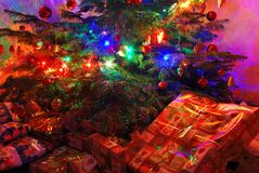 Many wrapped presents under a lit Christmas tree Stock Photos