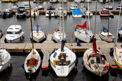 Many yachts and sailboats moored at the dock in the parking lot stock image