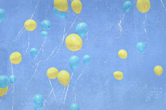Many yellow and blue balloons flying up in the sky. Grunge background with balloons. Holiday event Royalty Free Stock Photos