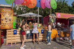 Many young happy people buying drinks at outdoor pop-up cafe Royalty Free Stock Images