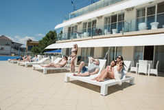 Many young men and women rest on the hotel`s summer area. Group of happy, beautiful and young people are relaxing and Stock Image