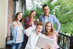 Group of teens using tablet on a cafe background. Happy friends with tablet. Modern lifestyle concept. Stock Photos