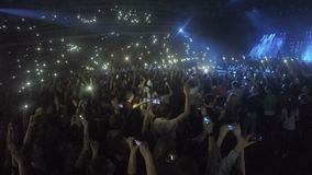 Many young people filming concert on smartphones. Addiction to gadgets, problem