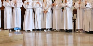 Many young people at first communion. In the church during the holy mass royalty free stock image