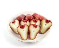Manzana color de rosa fresca en la placa blanca Imágenes de archivo libres de regalías